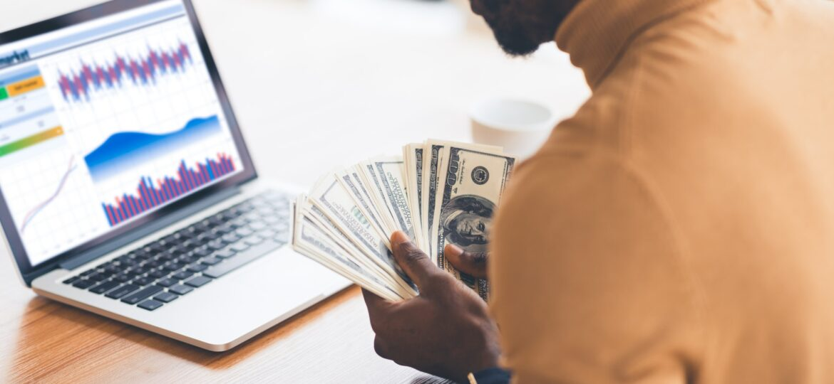 Black manager working with diagrams on pc holding dollars